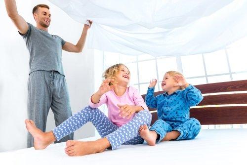 Padre giocando con i bambini nel materasso