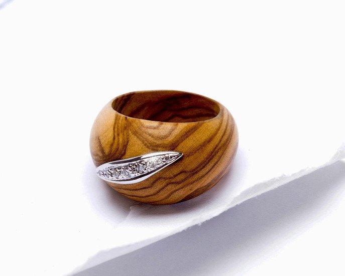 un anello in legno con un disegno in argento e delle perline