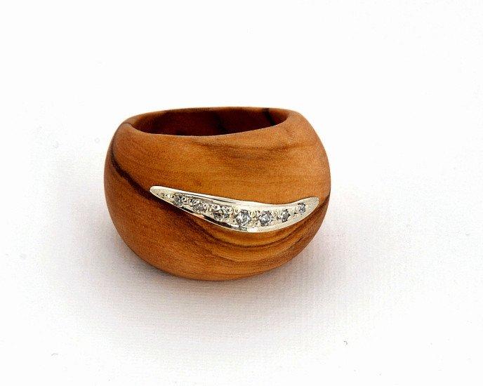 un anello in legno con un disegno in argento e delle perline brillanti