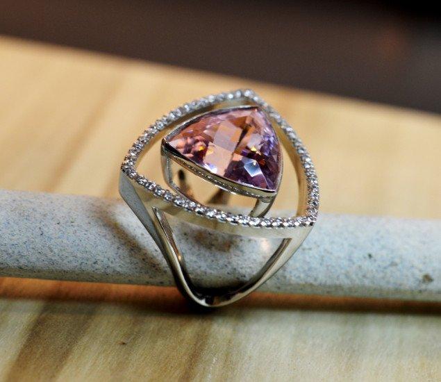un anello d'argento a forma triangolo con una pietra di color viola e zirconi