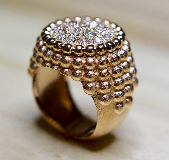 un anello d'oro con un disegno di una montagna e delle perline