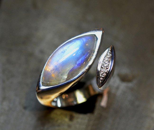 un anello con una pietra di luna e degli zirconi