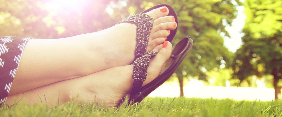 a pair of feet in flip flops in a sunny meadow