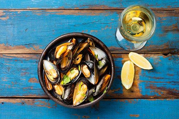 Cozze in ciotola di argilla, bicchiere di vino bianco e limone