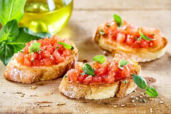 Gustosi pomodori salati antipasti italiani, o bruschetta, su fette di baguette tostate guarnite con basilico