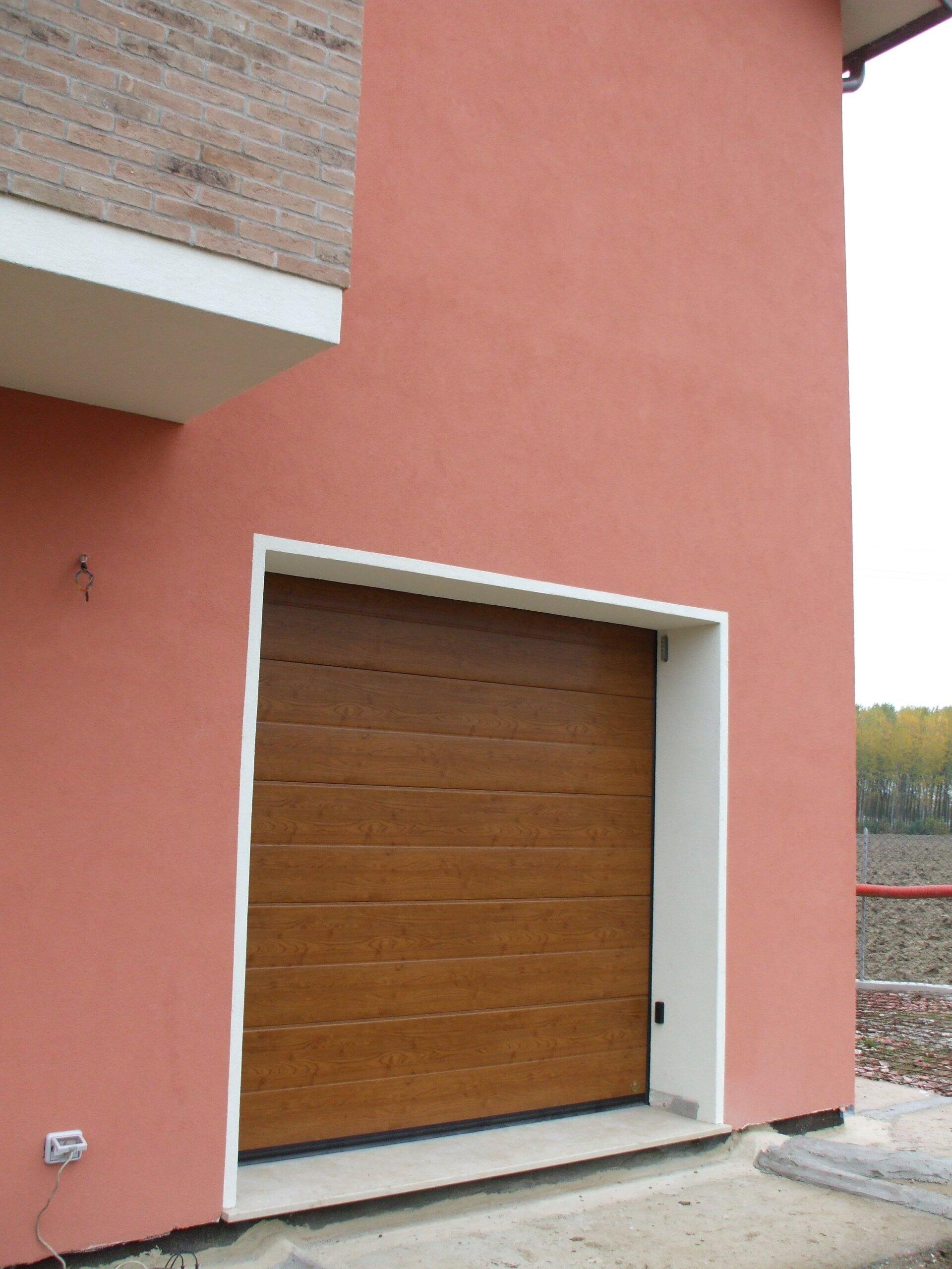 garage con serrande chiuse in una costruzione rosa