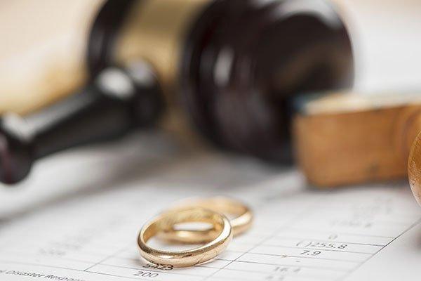 anelli di nozze appoggiati sopra un documento con vicino il martello del giudice
