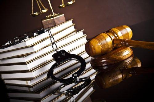 pila di libri manette martello del giudice e bilancia