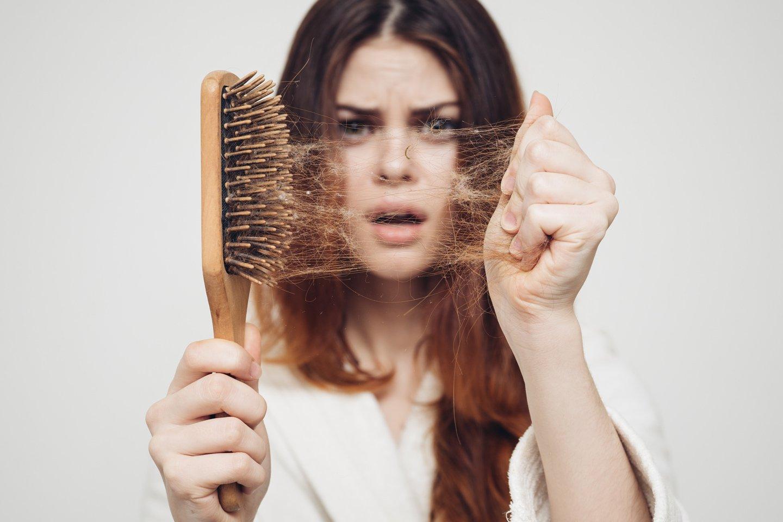 donna toglie capelli da spazzola