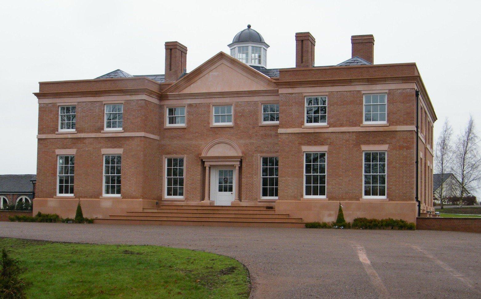 white windows on a big brick house