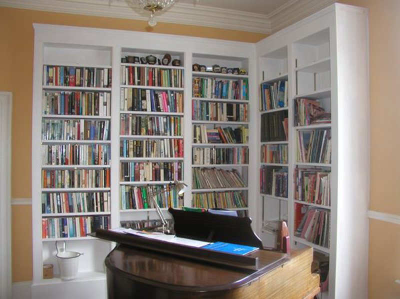 White fitted shelving full of books