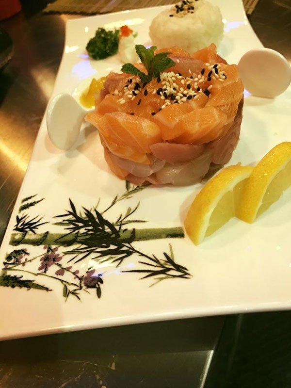 un piatto di tartare di salmone e due fette di limone