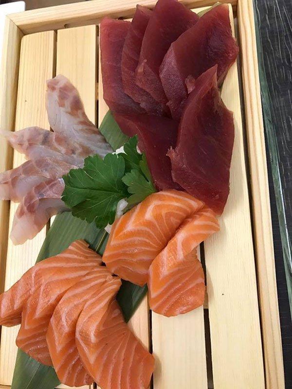 un tagliere con tonno, pesce spada e salmone tagliati in filetti da sushi