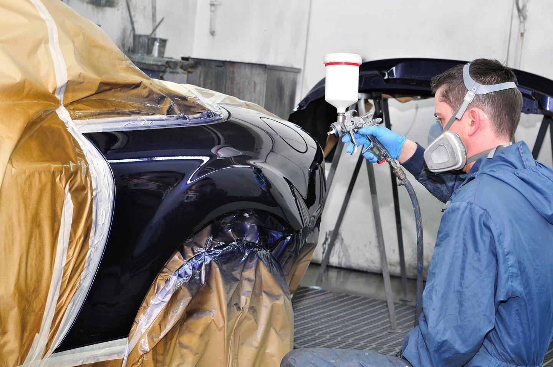 meccanico applica colore alla carrozzeria di un'auto con aerografo professionale