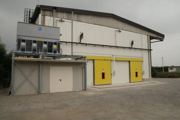 capannone bianco con porte gialle