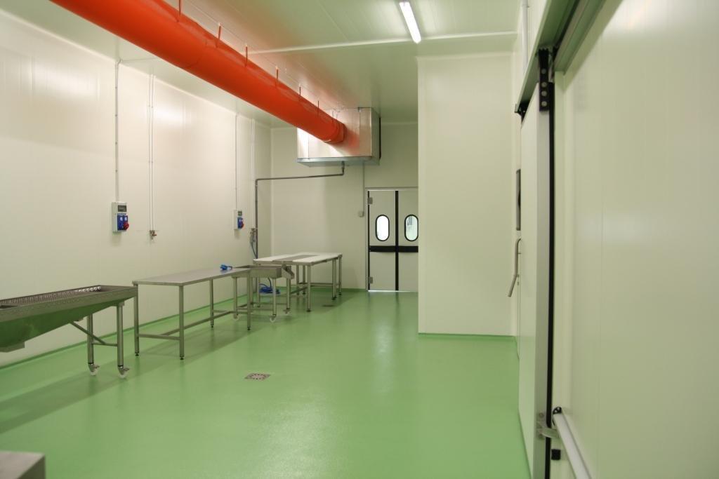 cella frigorifera vuota con pavimento verde acqua e tubi arancioni