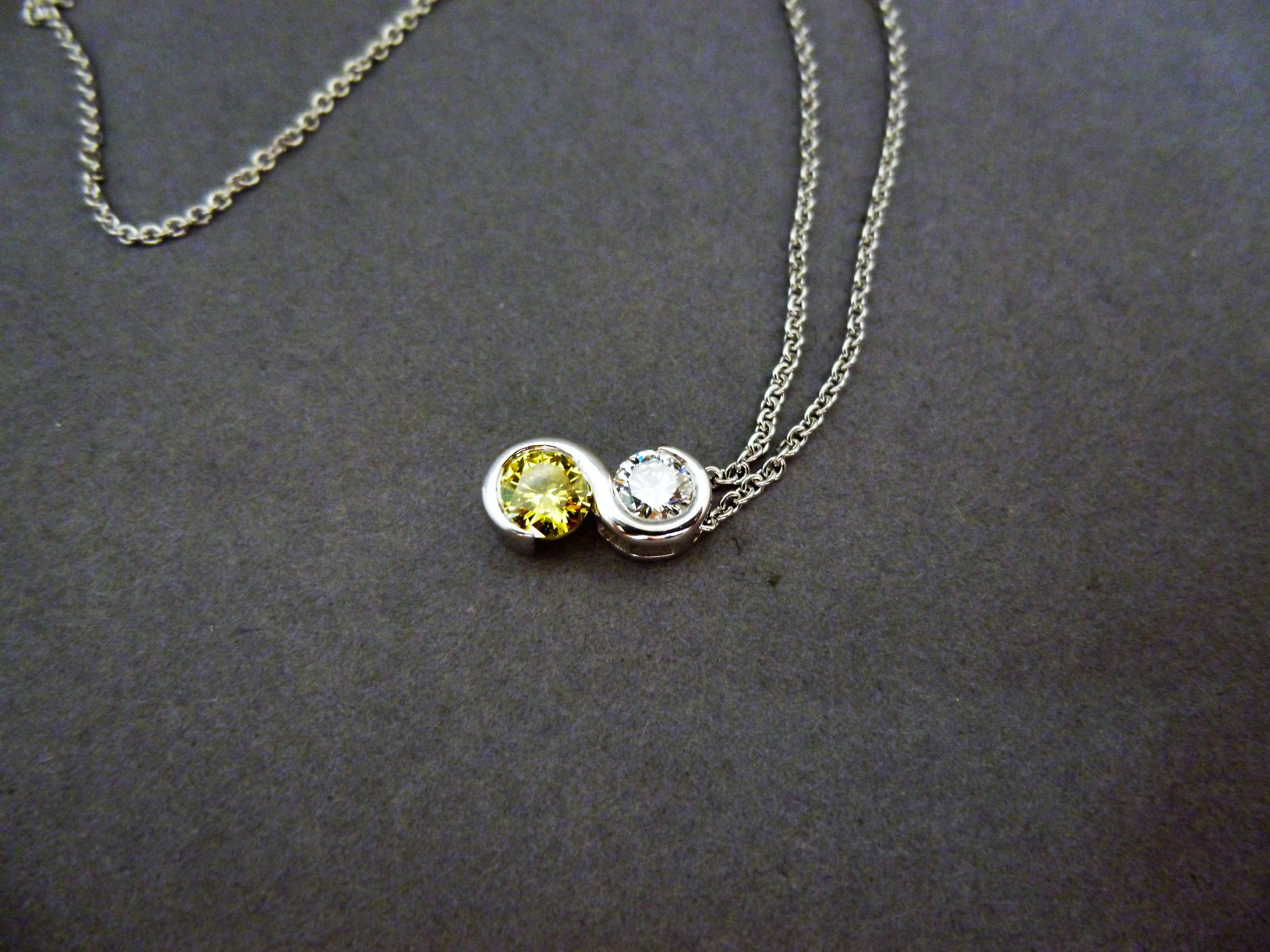 A yellow and white diamond pendant laid down