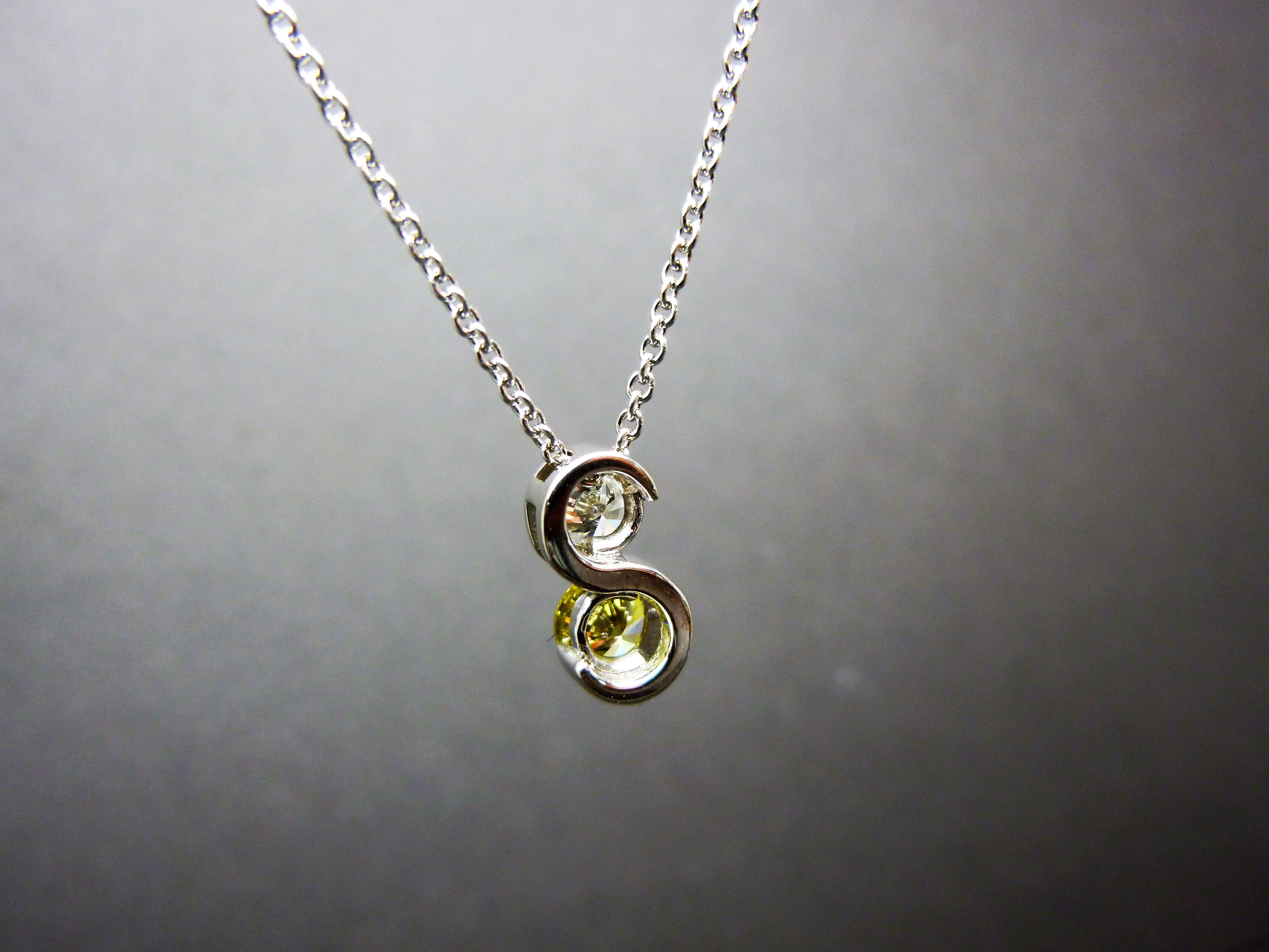 A yellow and white diamond pendant hanging