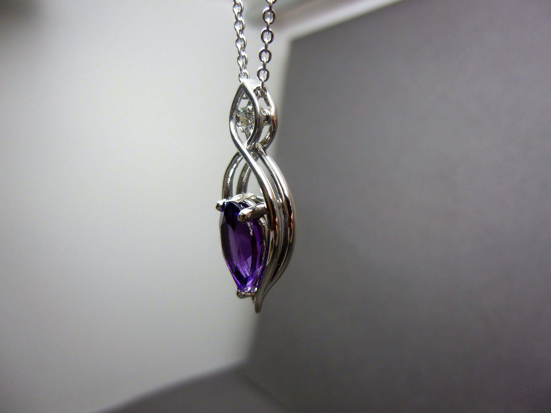 An amethyst and diamond pendant hanging