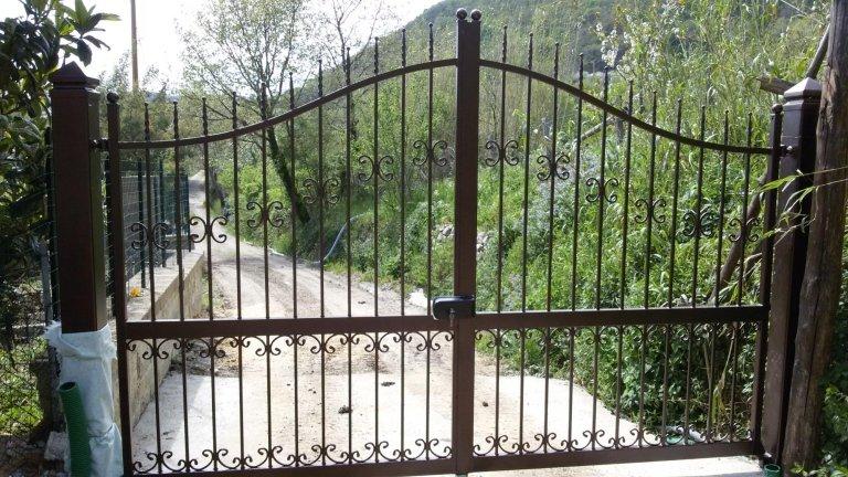 un cancello grande in ferro battuto di color grigio