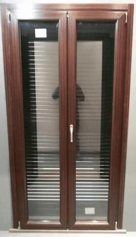 una finestra con rifiniture in legno chiaro e un inferriata