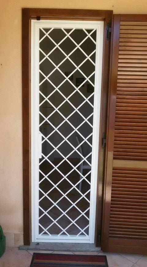 Finestra protetta con una griglia bianca di progettazione diagonale