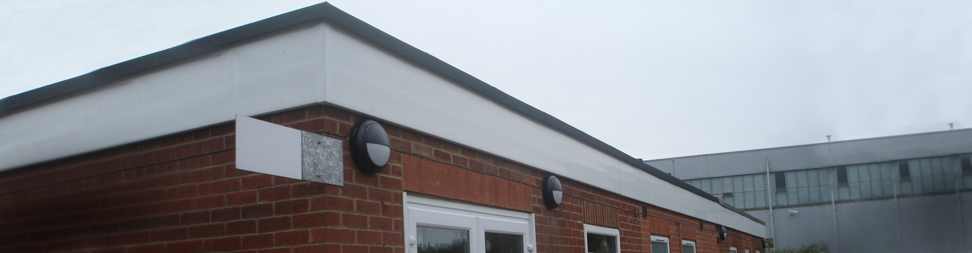 A building with a flat roof that has been worked on by Accurate Flat Roofing