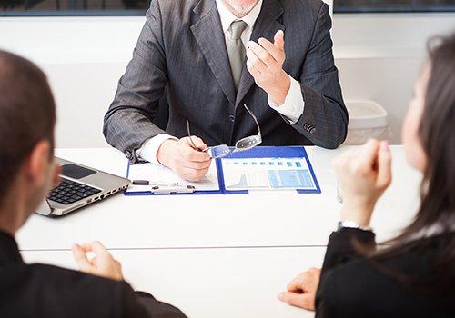 uomo in abito formale durante una consulenza a due persone