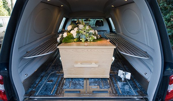 interno di un carro funebre e all'interno una bara in legno chiaro con un mazzo di fiori sopra