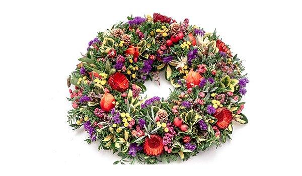 ghirlanda di fiori viola,gialli e rossi su uno sfondo bianco