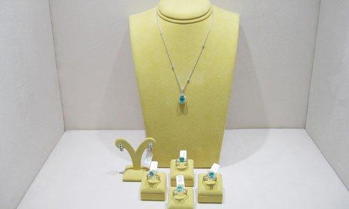 un porta parure giallo con un pendente con una pietra verde smeraldo e sotto degli anelli dello stesso stile esposti