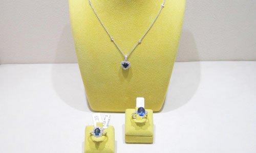 un porta parure giallo con un pendente con una pietra blu e sotto due anelli