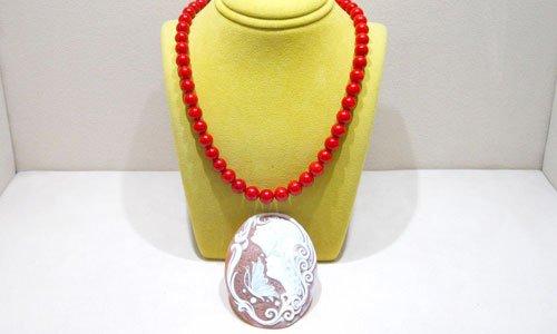 una collana a perle rosse con un grosso pendente di color rosa a fiori bianchi
