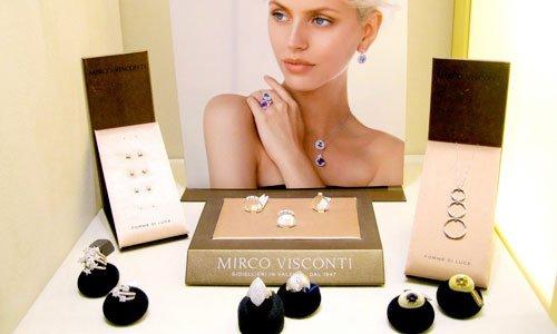una foto di una donna bionda con i capello corti e sotto una scatola con scritto Mirco Visconti e accanto e sopra alcuni anelli