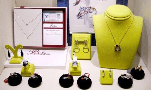 esposizione di anelli con pietre colorate, una collana a perle rosse,altre collane con perle e pendenti con pietre preziose colorate