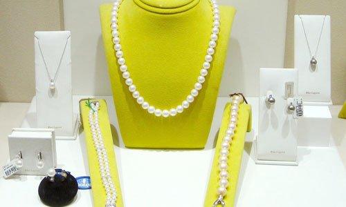 una collana di perle su un porta collana giallo, dei braccialetti in perle e altre creazioni come pendenti e orecchini in scatoline bianche