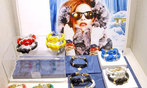 dei braccialetti stile fune legata di diversi colori e una foto di una donna con i capelli rossi e degli occhiali da sole neri