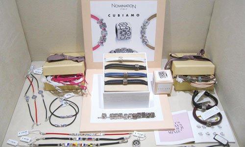 insieme di braccialetti di diversi colori in scatole bianche e beige e una foto pubblicitaria con scritto Nomination Italo Cusiamo
