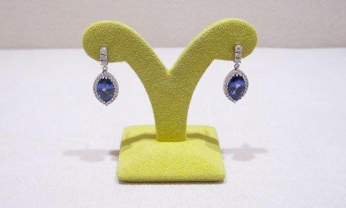 due orecchini con pietre preziose blu appesi su un porta orecchini giallo