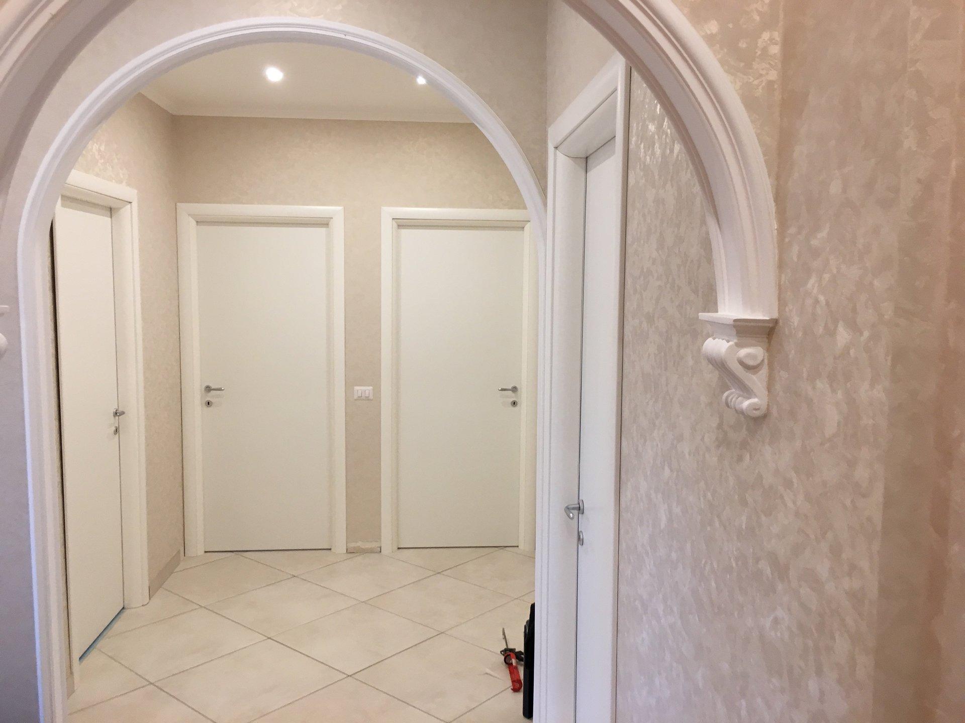 porte bianche su corridoio con archi
