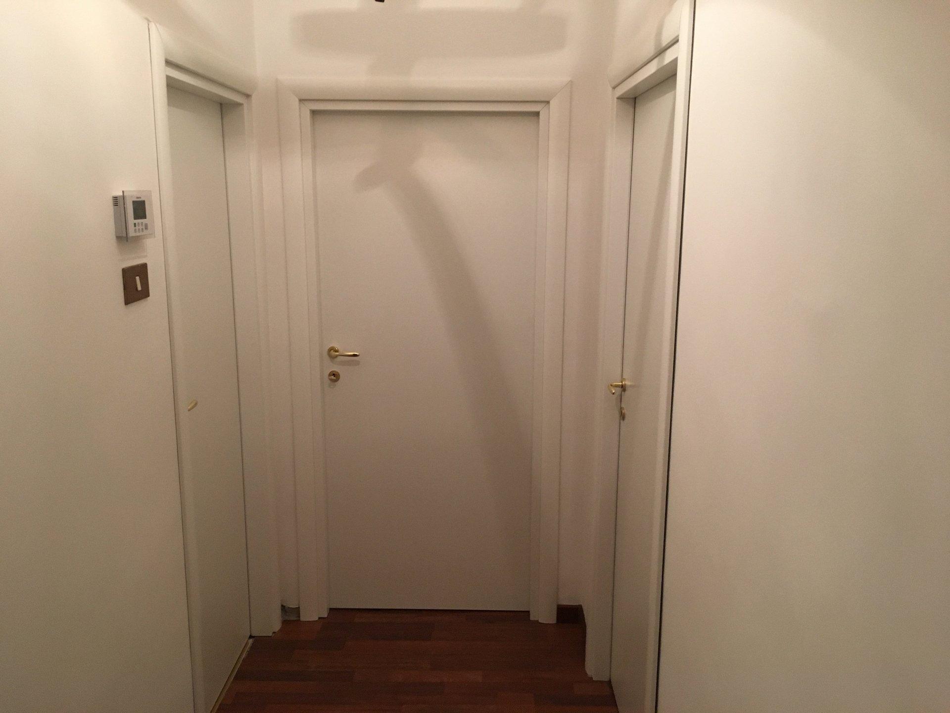 tre porte bianche all'interno di un appartamento