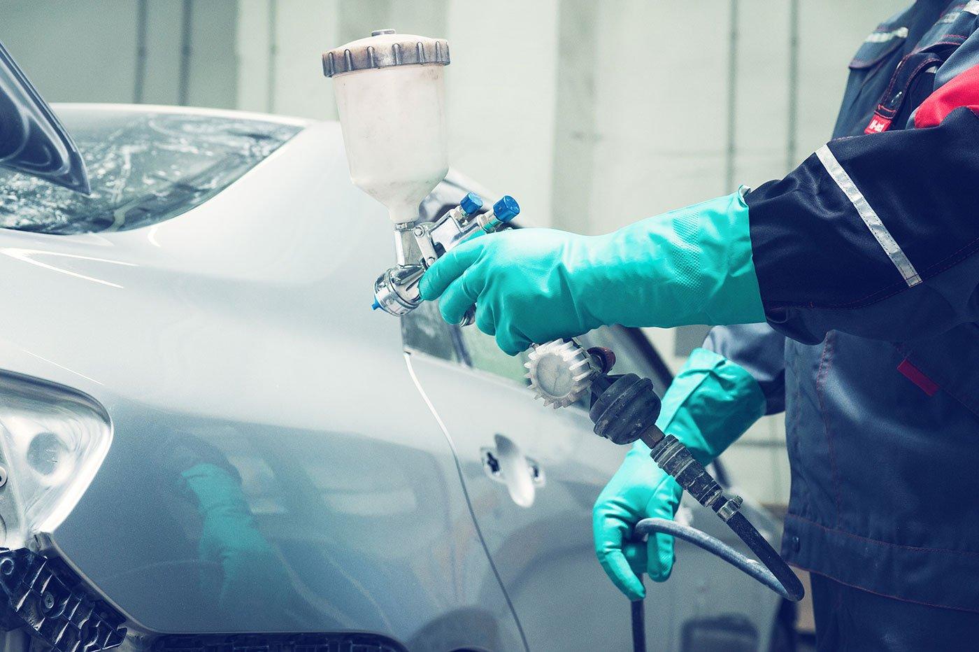 operaio vernicia un auto con pistola a spruzzo