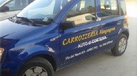 una vettura sostitutiva blu con scritto Carrozzeria Magagna