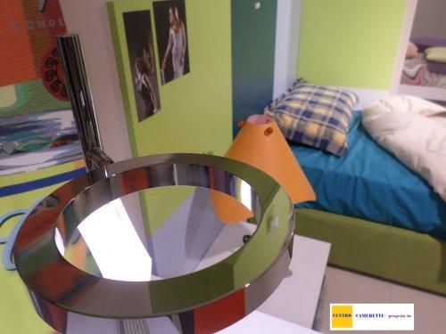un letto singolo di color verde e un comodino