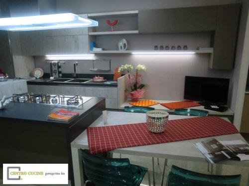 una cucina con doppi lavandini e una penisola con dei fornelli