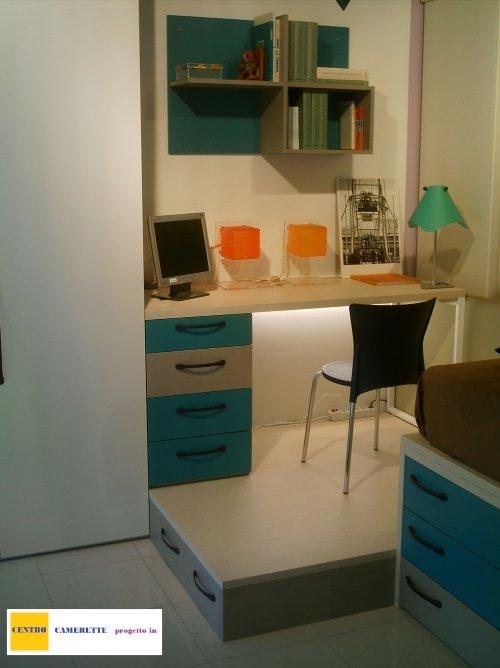 una scrivania con dei cassetti e delle mensole di color azzurro