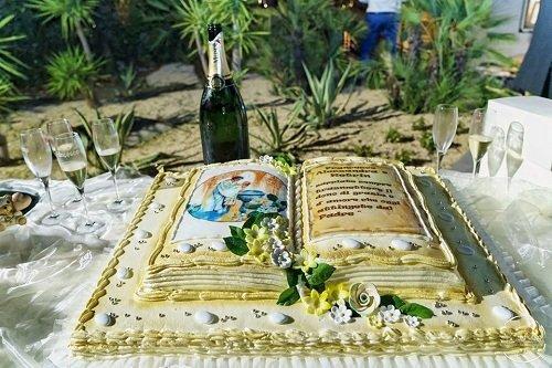 una torta a forma di libro, dei bicchieri e una bottiglia di champagne