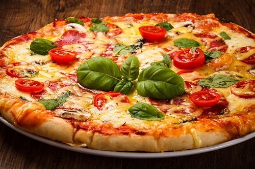 una pizza margherita con una foglia di basilico