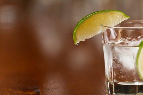 un bicchiere con un cocktail con ghiaccio e una fetta di lime