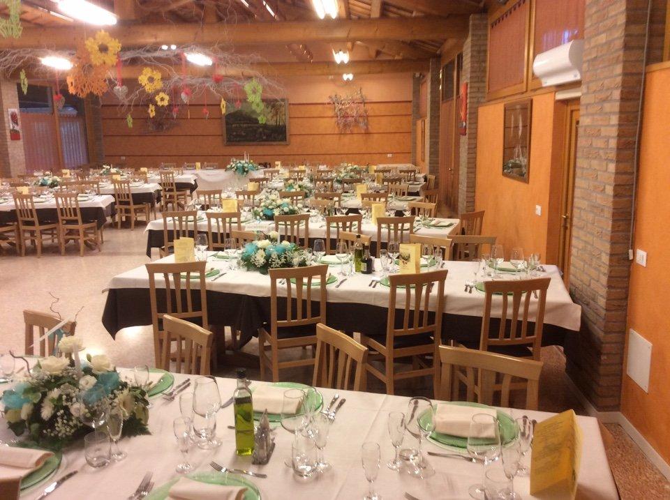 Altra vista del ristorante per un matrimonio,con fiori a tutti i tavoli e impiccando del tetto girasoles giganti